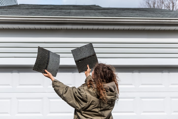 Woman examines roof damage Page: https://www.mauslawfirm.com/property-damage/roof-damage-claims/